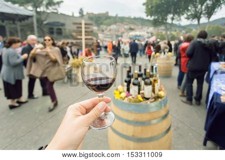 Glass of wine at tasting area of annual city festival Tbilisoba with crowd of people around. Tbilisi, the capital of Georgia country