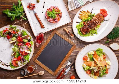 Different salads and Black Chalk Board top view. Vegetable salad Salad with smoked duck Grilled chicken Caesar salad. Copy space.