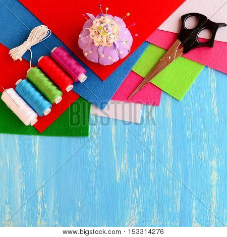 Colored felt sheets, sewing kit, scissors, pins, pincushion, white ribbon on blue wooden background with empty space for text. Sewing supplies. Needlework concept