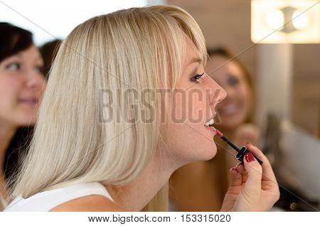 Attractive Blond Woman Applying Lipstick