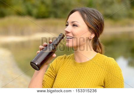 Happy Young Woman Drinking Beer At A Picnic