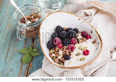 Homemade granola with blackberry and milk close-up. Healthy breakfast ingredients. Rustic style. Vintage toned
