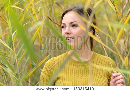 Pensive Young Woman Standing In Reeds