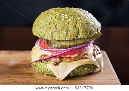blue burger cutlet vegetables and cheese with sauce on a wooden board