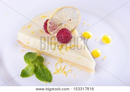 piece French lemon tart garnished with fresh raspberries mint and slice of lemon