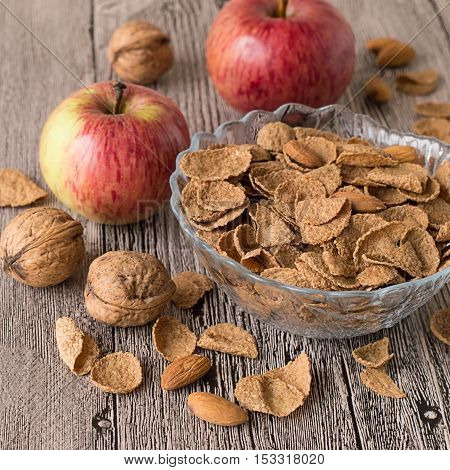 Vase with dry oat flakes, two apples, walnuts and almonds on a gray wooden table.