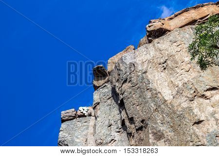 Up view photo of a steep rock cliff against a deep blue sky
