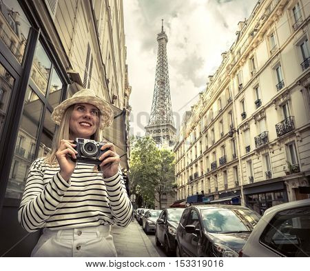 Woman tourist with camera on the street near the Eiffel tower in Paris under sunlight and blue sky. Famous popular touristic place in the world.