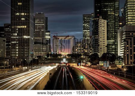 Modern city at night with cars light lines.