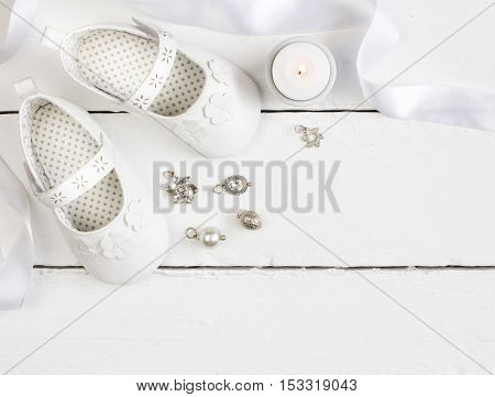 Overhead photo of pair of white baby booties candle ribbon and charms on white painted table