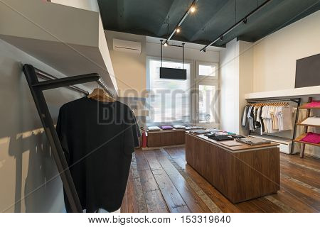 Interior of modern urban fashion clothes t-shirt store