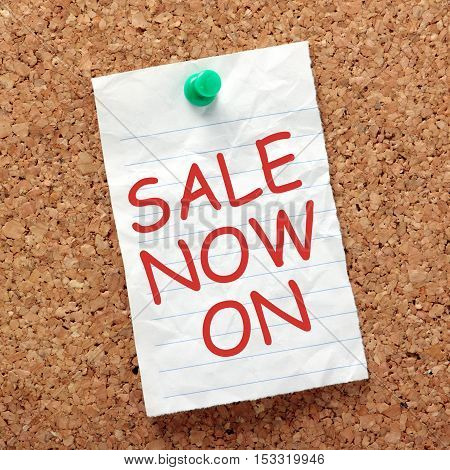 The words Sale Now On in red ink on a piece of crumpled lined paper pinned to a cork notice board as a reminder