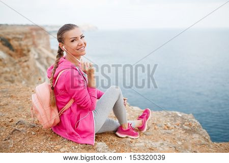 Beautiful brunette woman with long hair braided in a braid, brown eyes, lovely smile and white teeth, dressed in gray sweat pants, pink sneakers and pink blazer behind light pink backpack sits on the edge of a cliff on the background of blue sea
