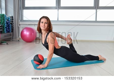 Fitness, sport, exercising lifestyle - Fit woman doing stretching exercises in a gym.