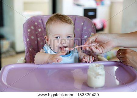 Cute baby with blond hair and blue eyes, wearing a blue shirt, sitting at a table purple for feeding babies, eat cheese from a pink spoon that feeds his mom