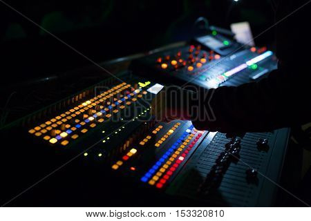 Soundman working on the mixing console. Hands on the sliders.