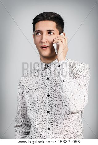 Portrait of young man talking on the phone over gray background