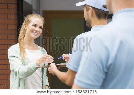 Courier Making A Delivery To Woman