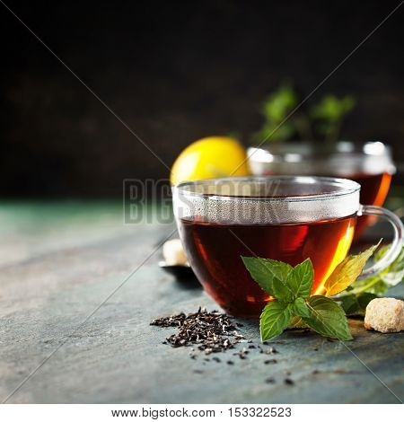 Hot tea cup with mint and sugar on rustic background