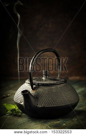 Image of traditional eastern teapot on wooden desk