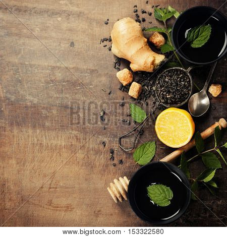 Tea with mint, ginger and lemon on wooden background (asian food concept)