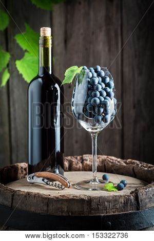 Tasty Red Wine And Fresh Grapes On Barrel