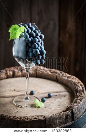 Ripe Red Grapes In Broken Glass On Wooden Barrel