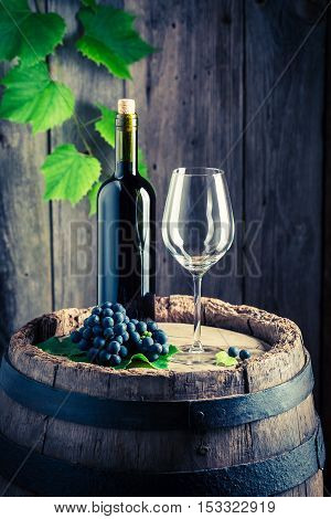 Red Wine, Empty Glass And Grapes On Barrel