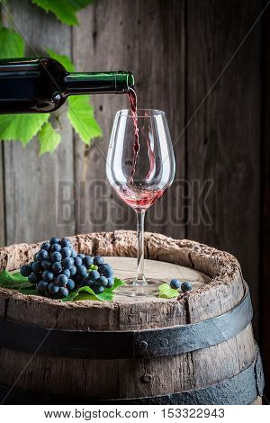 Pouring Red Wine On Glass On Barrel With Grapes
