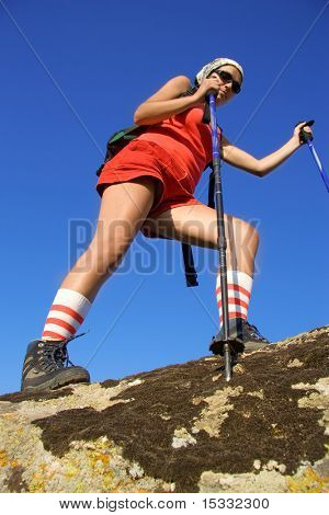 Young woman climbing a cliff