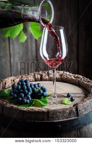 Pouring Red Wine From Carafe Into A Glass On Old Barrel