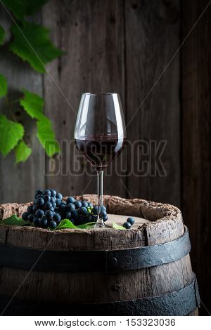 Fresh Red Wine On Barrel With Grapes
