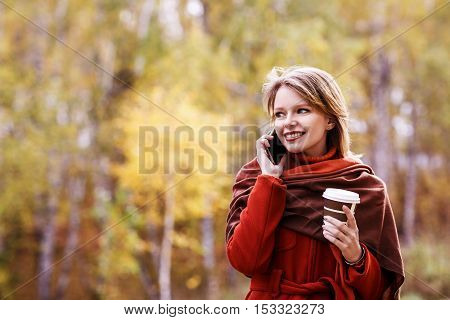 Business woman with to go coffee in autumn park