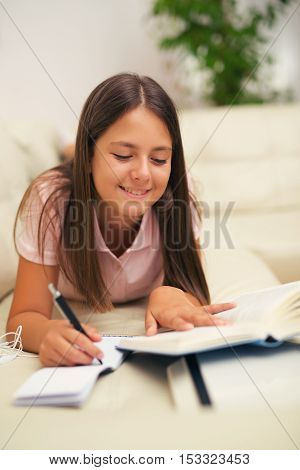 Girl writing in a notebook lying on the bed