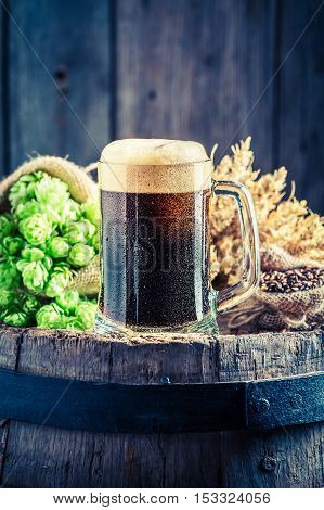 Pint Of Dark Beer, Wheat And Hops On Old Barrel
