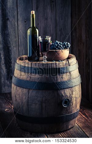 Glass Full Of Wine With Fresh Grapes On Wooden Barrel
