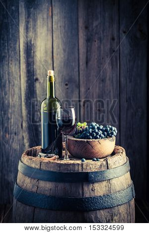 Red Wine With Fresh Grapes On Old Barrel