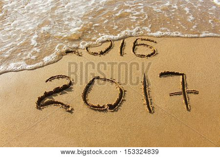 2016 and 2017 year written on sandy beach sea.