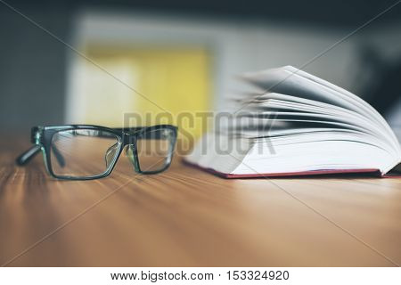Closeup of glasses and open book on wooden desktop. Knowledge concept