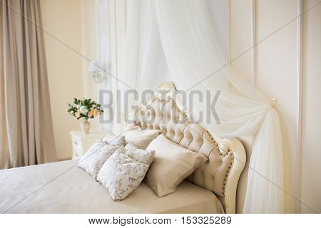 Bedroom in soft light colors. Big comfortable double bed in elegant classic interior.