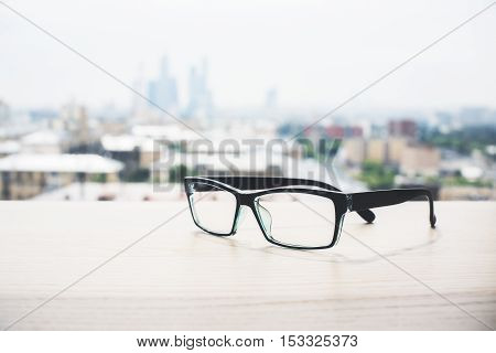 Close up of eyeglasses placed on wooden surface. Blurry city view background
