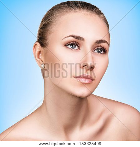 Beautiful young woman face over blue background