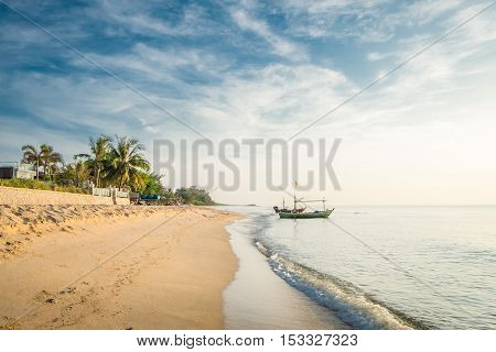 Beautiful blue sea wave and fishing boat on white sand beach for vacations in Hua Hin Prachuap Khiri Khan Province, Thailand.