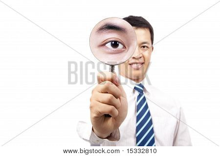 young businessman holding Magnifier and show his big eye