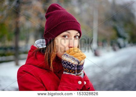 Young girl warms his hands with his breath mittens on the hands Autumn day and the first snow. The girl in a red coat and red hat walks in the park.