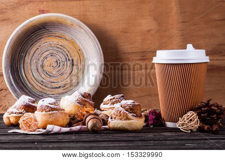 Cinnamon bun and coffee cup on wood background. Home baking