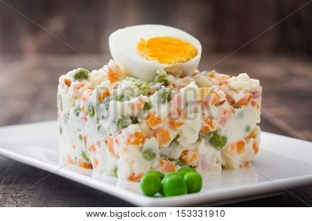 Russian salad on a rustic wooden table