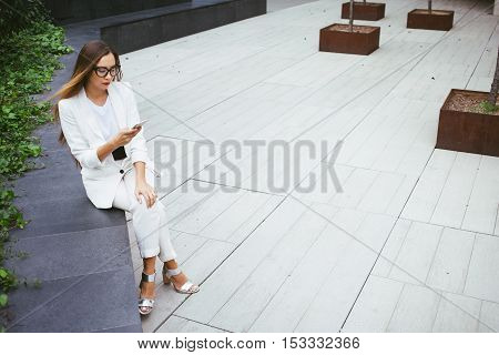 Young attractive businesswoman with long hair is using smart-phone sitting in a backyard near office building. Gray background with copy space area for your text o design.