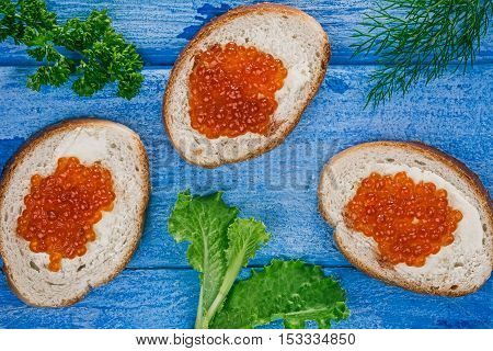 Toasts with salted salmon roe and fresh potherbs over sky-blue wood plank background. Closeup. Flat lay
