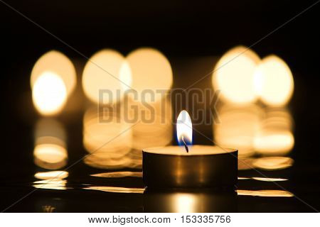 Single candle burning in darkness with reflection of candlelight in the background